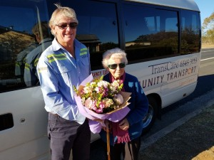 Mavis Marsden Lynch  being presented with a bunch of flowers from TransCare bus driver Chris Gill to celebrate her 100th birthday.